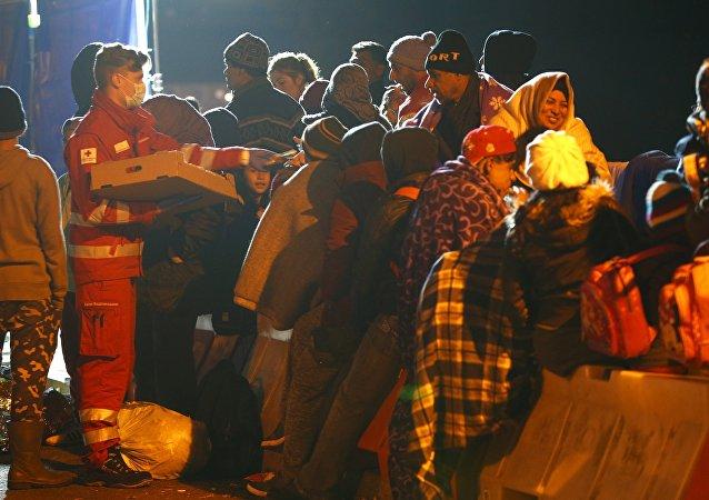 Migrants wait on the bridge at the Austrian-German border between Braunau and Simbach at lake Inn near Passau, Germany, October 27, 2015