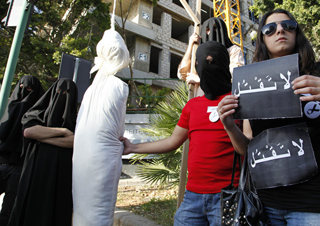 Activists from a civil organization reenact an execution scene in front of the Saudi Arabia Embassy in Beirut, Lebanon, Thursday, April 1, 2010, as they protest a possible beheading of a Lebanese man accused of witchcraft in Saudi Arabia. The lawyer of Lebanese TV psychic Ali Sibat who was convicted in Saudi Arabia for witchcraft said Thursday her client could be beheaded this week and urged Lebanese and Saudi leaders to help spare his life. The Arabic writing on banners read:don't kill.
