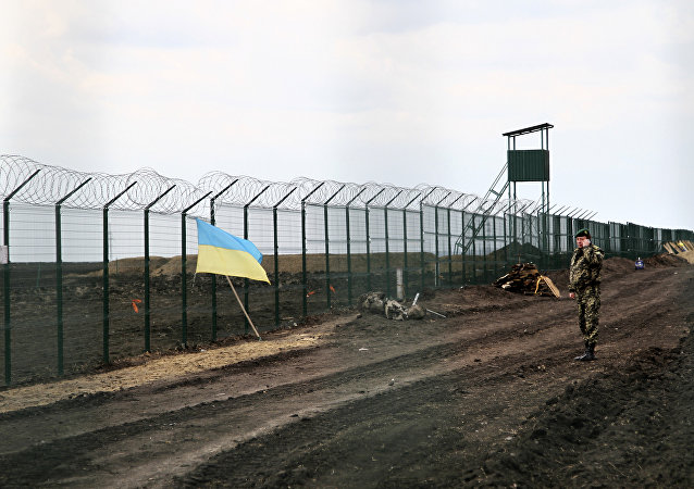 Ukrainian border guard officer speaks on a phone near a national flag attached to the fence on the Ukrainian-Russian border near Hoptivka, Kharkiv region, eastern Ukraine