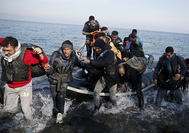 Refugees and migrants jump off an inflatable raft as they arrive on the Greek island of Lesbos, November 11, 2015