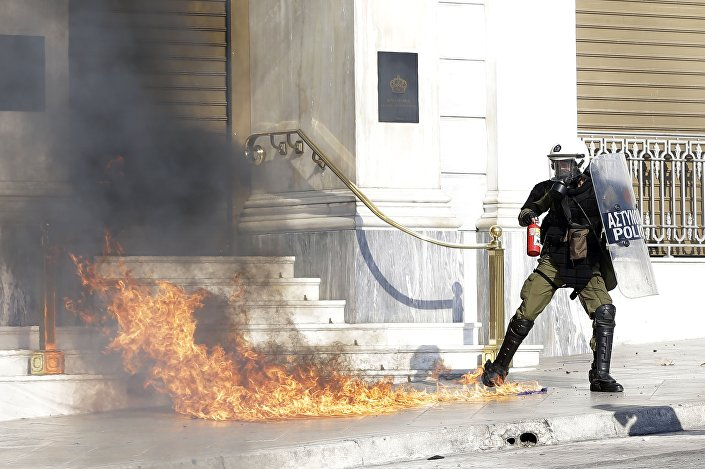 A riot policeman tries to avoid a petrol bomb thrown by protesters during a rally in Athens, Thursday, Nov. 12, 2015.