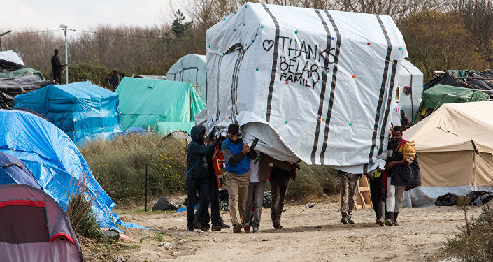 Migrant men move a tent in the New Jungle migrant camp in Calais on November 12, 2015.