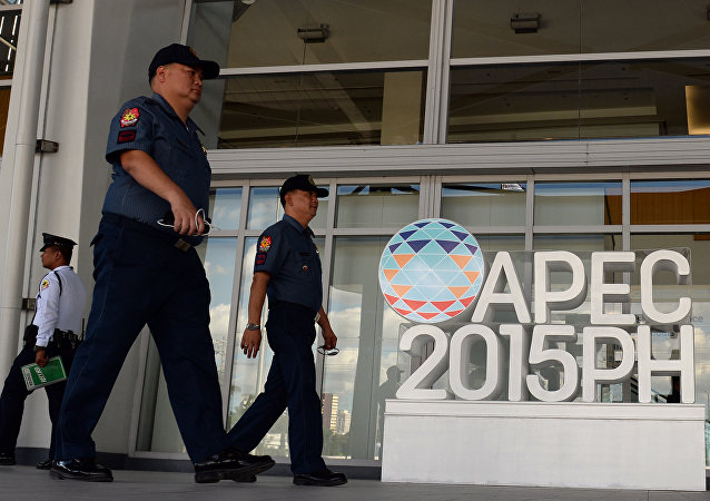 Philippine policemen walk past an Asia Pacific Economic Cooperation (APEC) summit logo in front of the media centre in Manila on November 11, 2015