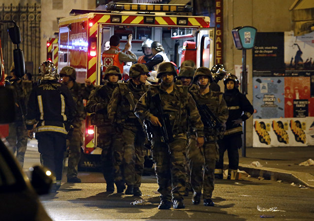 Soldiers walk in front of an ambulance as rescue workers evacuate victims near La Belle Equipe, rue de Charonne, at the site of an attack on Paris on November 14, 2015