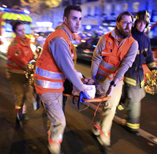 A woman is being evacuated from the Bataclan theater after a shooting in Paris, Friday Nov. 13, 2015