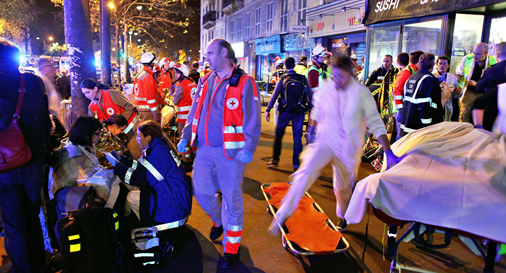 People rest on a bench after being evacuated from the Bataclan theater after a shooting in Paris, Saturday, Nov. 14, 2015