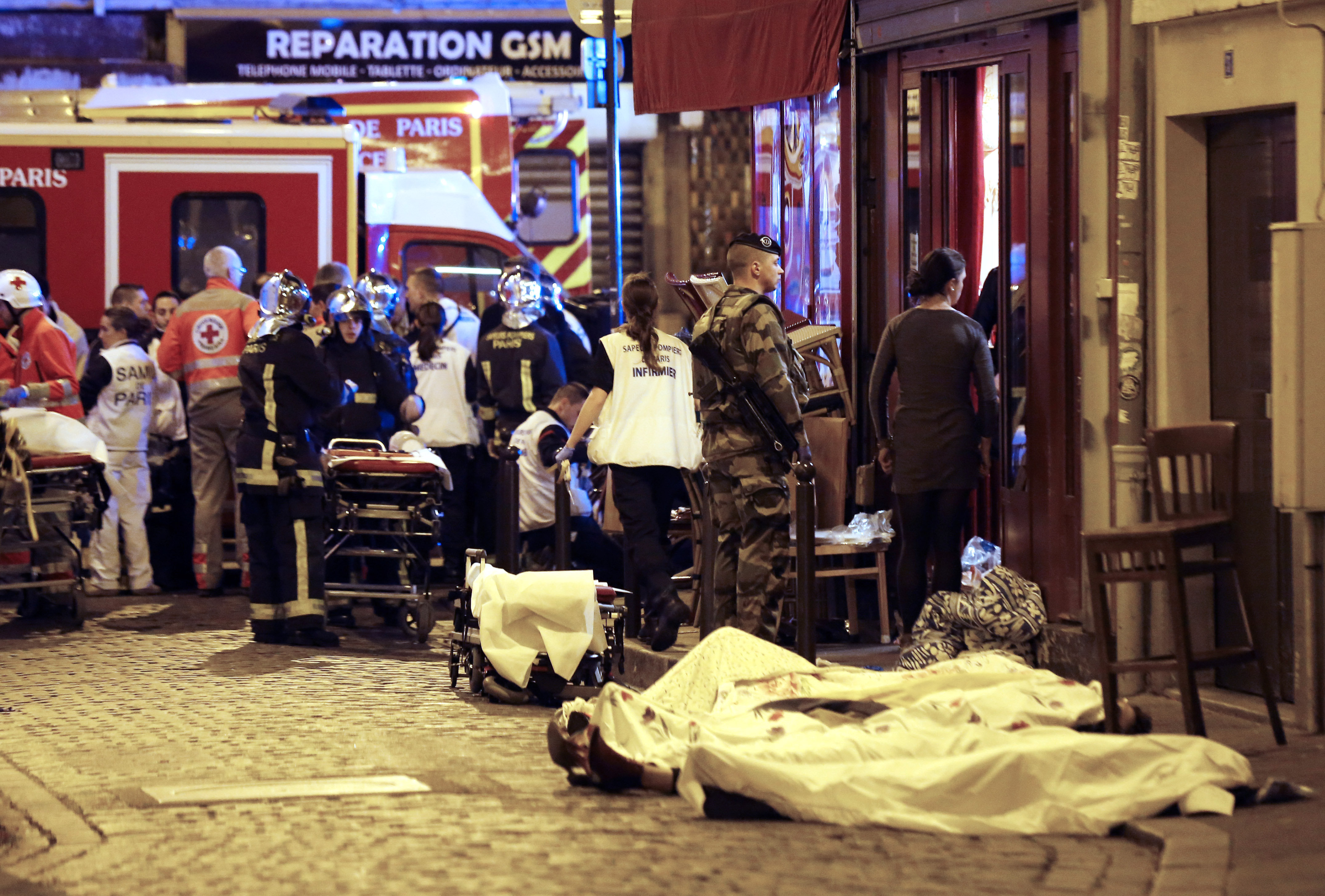 A soldier stands by victims in the10th district of Paris, Friday, Nov. 13, 2015.