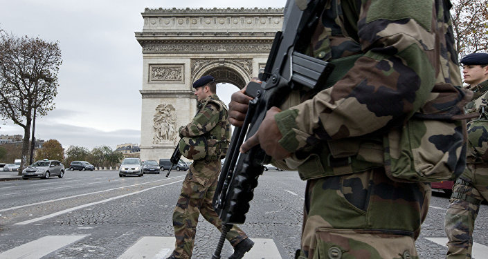 French soldiers cross the Champs Elysees avenue passing the Arc de Triomphe in Paris, Monday, Nov. 16, 2015