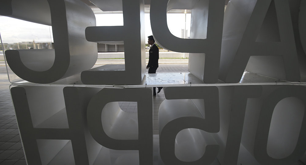 A man walks in front of the APEC 2015 logo in Manila, Philippines on Sunday, Nov. 15, 2015