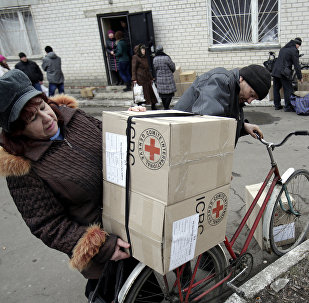 File photo of the residents of the eastern Ukrainian city of Avdiivka, in the Donetsk region controlled by Ukrainian forces, carry boxes containing Red Cross humanitarian aid in Avdiivka on March 2, 2015