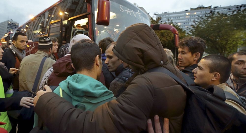 Migrants board buses after their evacuation from the Lycee Jean Quarre, an empty secondary school occupied by hundred of migrants and asylum seekers in the 19th district in Paris, France, October 23, 2015.