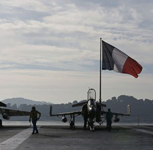 Flight deck crew work around a Rafale (L) and a Super Etendard fighter jets as a French flag flies aboard the French nuclear-powered aircraft carrier Charles de Gaulle before its departure from the naval base of Toulon, France, November 18, 2015