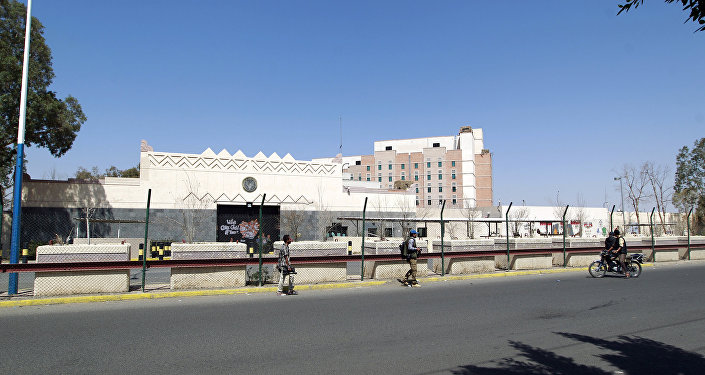 Yemenis walk past the compound of the US embassy in the Yemeni capital Sanaa