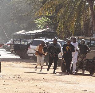 People run to flee from the Radisson Blu Hotel in Bamako, Mali, Friday, Nov. 20, 2015.