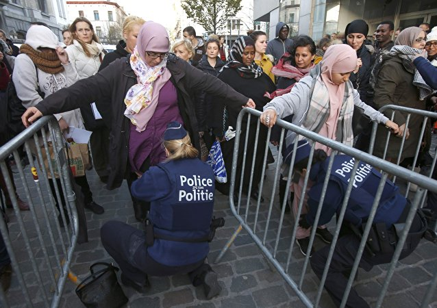 Residents of the Brussels suburb of Molenbeek are searched by police vefore taking part in a memorial gathering to honour the victims of the recent deadly Paris attacks, in Brussels, Belgium, November 18, 2015