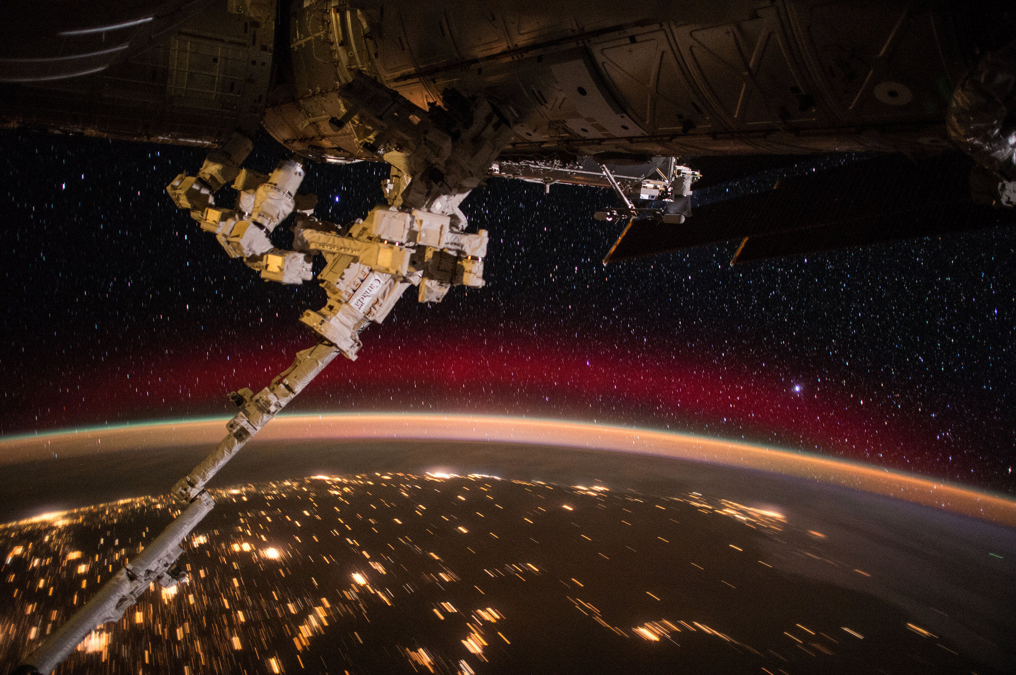 International Space Station crew members captured this view of the station's remote controlled Canadarm protruding from the orbiting laboratory, with Earth's colorful aurora, sparkling city lights and a rising sun over a background of stars.