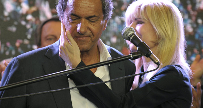 Buenos Aires province governor and presidential candidate for the Frente Para la Victoria (Front for Victory) Daniel Scioli (C) as he is comforted by his wife Karina Rabolini at the party's headquarters after admitting his defeat to his rival, the Head of Government of the Autonomous City of Buenos Aires and candidate for the Cambiemos (Let's Change) party Mauricio Macri, in Buenos Aires, on November 22, 2015.