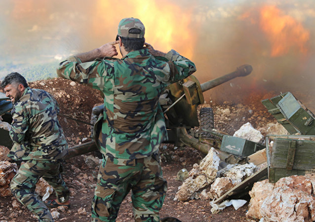 In this photo taken on Saturday, Oct. 10, 2015, Syrian army personnel fire a cannon in Latakia province, about 12 miles from the border with Turkey in Syria