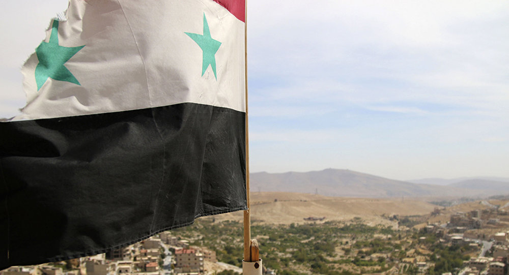 In this photo taken on Sunday, Oct. 18, 2015, a Syrian flag flies above the village of Maaloula, north of Damascus, Syria
