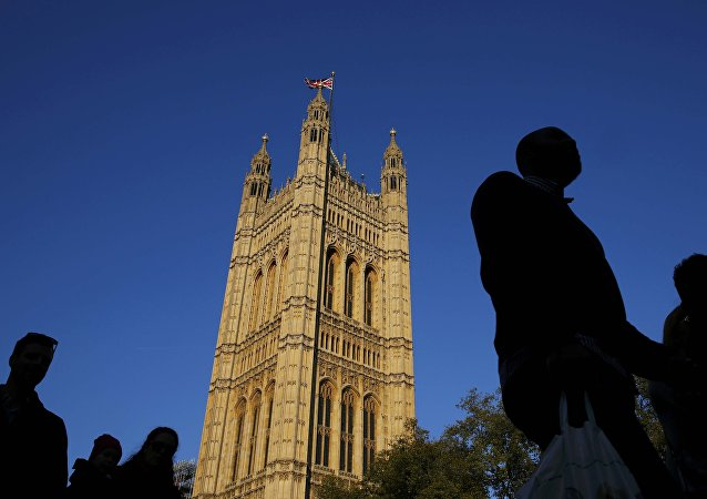 People are silhouetted against sky as they walk past the Houses of Parliament in central London, Britain October 26, 2015.