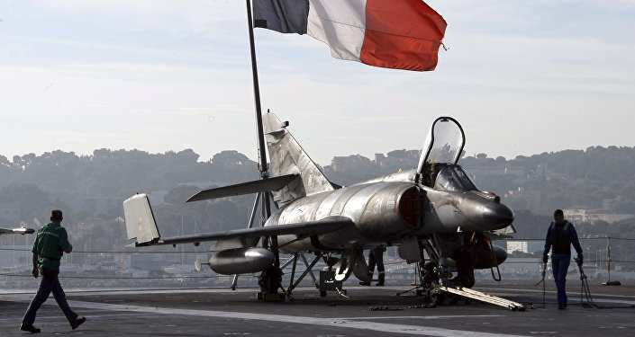 French sailors walk by a Super-Etendard jetfighter on the deck of France's nuclear-powered aircraft carrier Charles de Gaulle before to leave its home port of Toulon, southern France, Wednesday, Nov.18, 2015