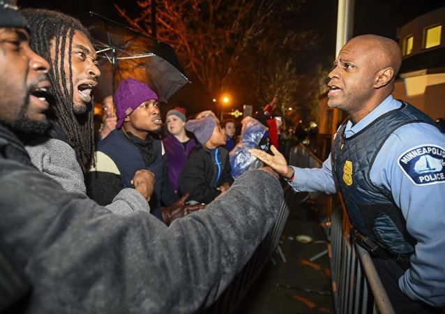 A police officer talks with demonstrators in front of a north Minneapolis police precinct during a protest in response to the shooting death of Jamar Clark by police officers in Minneapolis, Minnesota, November 18, 2015