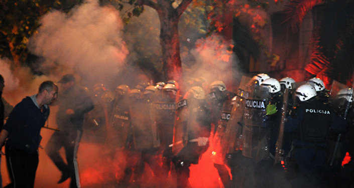 Montenegrin police officers are engulfed in smoke and flames as opposition supporters hurled torches on them during a protest in front of the Parliament building in Podgorica, Montenegro Saturday, Oct. 24, 2015. Police fired tear gas at opposition supporters who hurled fire bombs and torches to demand the resignation Prime Minister Milo Djukanovic's government which hopes to steer the Balkan country toward NATO membership later this year