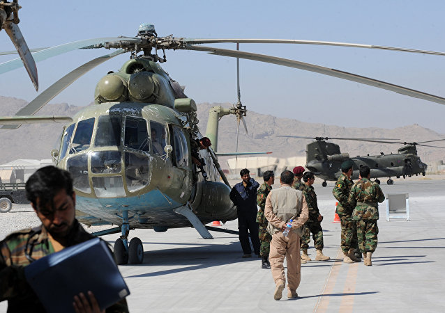 A group of Afghan Nationl Army Air Corps personnel gather beside the Russian Mi-17 transport helicopter in Kandahar air base.