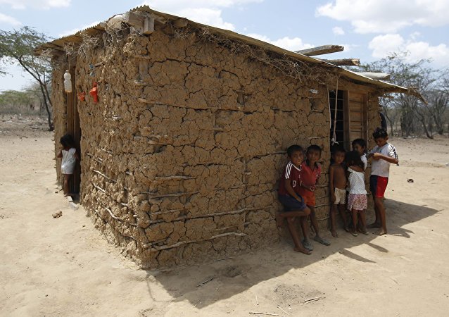Wayuu indigenous children stand in the shade of their adobe home in Manaure, Colombia, Thursday, Sept. 10, 2015. Hunger exacerbated by a two-year-old drought is one of the biggest problems facing the Wayuu, a 600,000-strong ancestral tribe that's caught in the middle of Venezuela's crackdown on smuggling along its western border with Colombia