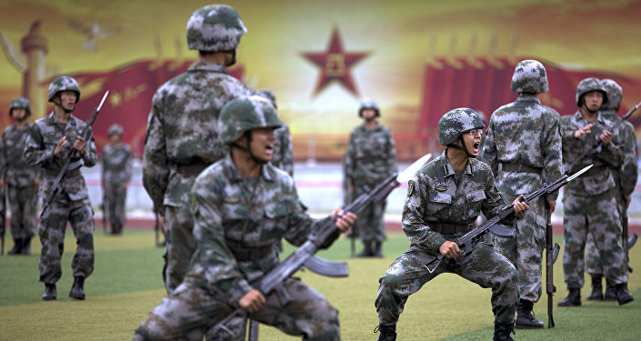 Chinese People's Liberation Army cadets shout as they take part in a bayonet drills at the PLA's Armoured Forces Engineering Academy Base, on the outskirt of Beijing, China Tuesday, July 22, 2014.