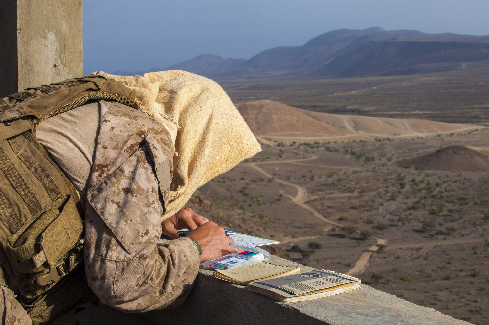 A 26th Marine Expeditionary Unit Maritime Raid Force Marine finds target locations on a map prior to conducting a joint terminal attack control training exercise at an observation post in Djibouti, Africa, May 30, 2013