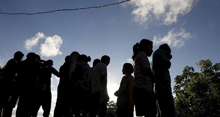 People stand near at a crime scene where seven men were killed, in Tegucigalpa, Honduras