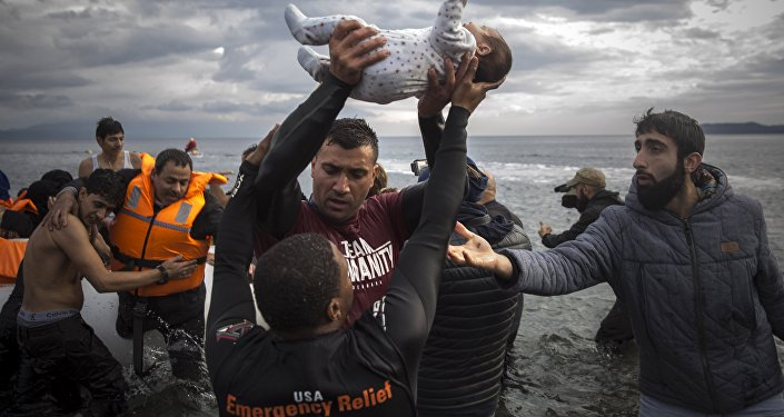 A volunteer holds up a baby as others help migrants and refugees to disembark from a dinghy after their arrival from the Turkish coast to the Greek island of Lesbos, Wednesday, Nov. 25, 2015.