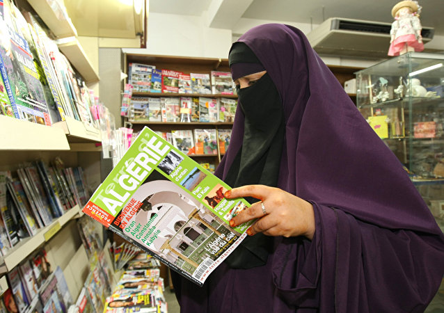 A woman wears a niqab , as she reads a magazine in a shop, in Avignon, southern France, Monday, Sept. 13, 2010.