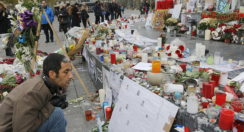 "A man reads messages at the Place de la Republique in Paris, Friday, Nov. 27, 2015. A subdued France paid homage Friday to those killed two weeks ago in the attacks that gripped Paris in fear and mourning, honoring each of the 130 dead by name as the president pledged to ""destroy the army of fanatics"" who claimed so many young lives."