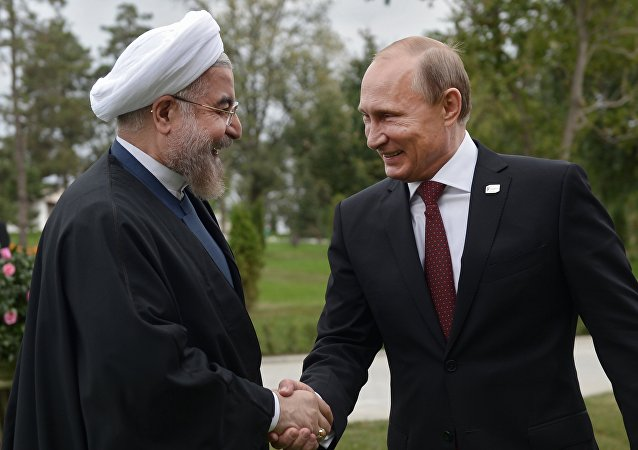 Iranian President Hassan Rouhani (L) shakes hands with his Russian counterpart Vladimir Putin