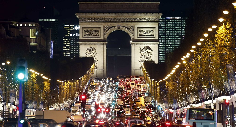 Christmas holiday lights hang from trees to illuminate Champs Elysees avenue in Paris as rush hour traffic fills the avenue leading up to the Arc de Triomphe, France, November 19, 2015