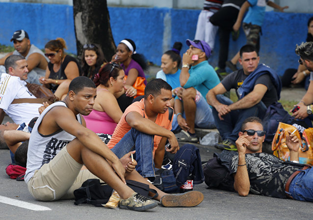 Cubans interrupt traffic sitting on a portion of Fifth Avenue near Ecuador's embassy to express discontent with a new visa rule that now requires Cubans have a visa to visit the South American country, in Havana, Cuba, Saturday, Nov. 28, 2015
