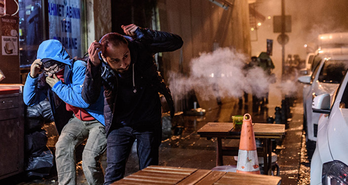 Protesters run for cover from tear gas fired by Turkish riot police during a demonstration on Istiklal avenue in Istanbul after a top Kurdish lawyer was killed in Diyarbakir on November 28, 2015