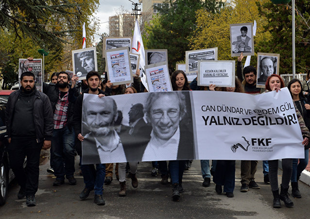 This file photo shows people demonstrating against the jailing of opposition Cumhuriyet newspaper's editor-in-chief Can Dundar and Ankara representative Erdem Gul, in Ankara, Turkey, Friday, Nov. 27, 2015