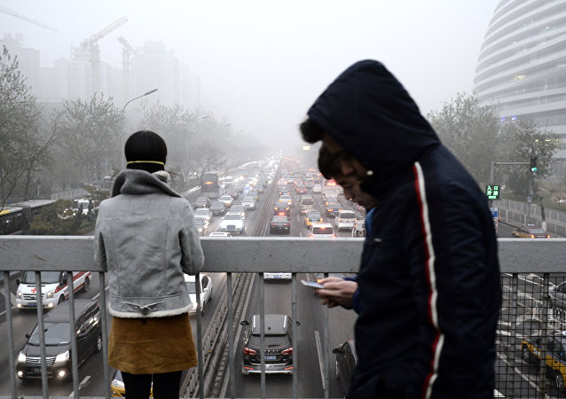 Pedestrians walk across a bridge in Beijing on December 1, 2015
