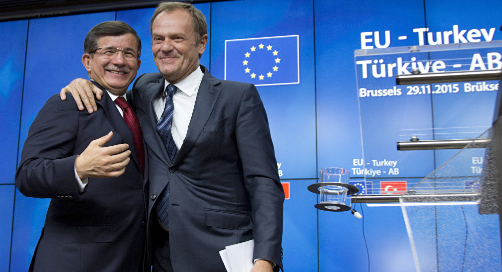 European Council President Donald Tusk, right, puts his arm on the shoulder of Turkish Prime Minister Ahmet Davutoglu