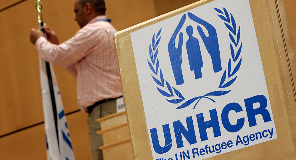 A staff installs a UNHCR flag close to a logo of UN High Commissioner for Refugees (UNHCR) prior to the opening of a two-day United Nations conference trying to boost support for Iraqis who have fled violence, 17 April 2007 at the UN Office in Geneva