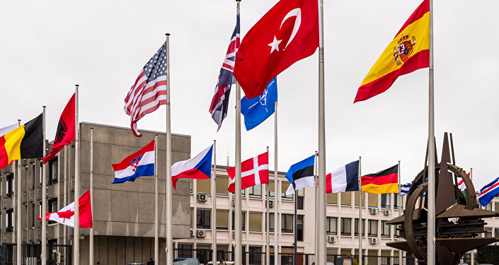 NATO country flags wave outside NATO headquarters in Brussels.