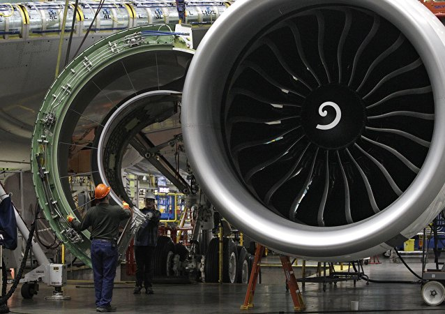 Worker maneuver the cover of a engine into place on a Boeing 777 jet at the company's manufacturing plant, Monday, Feb. 14, 2011, in Everett, Wash.