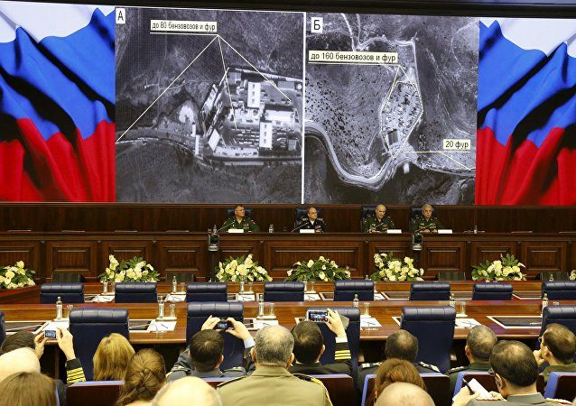 Defence ministry officials sit under screens with satellite images on display during a briefing in Moscow, Russia, December 2, 2015