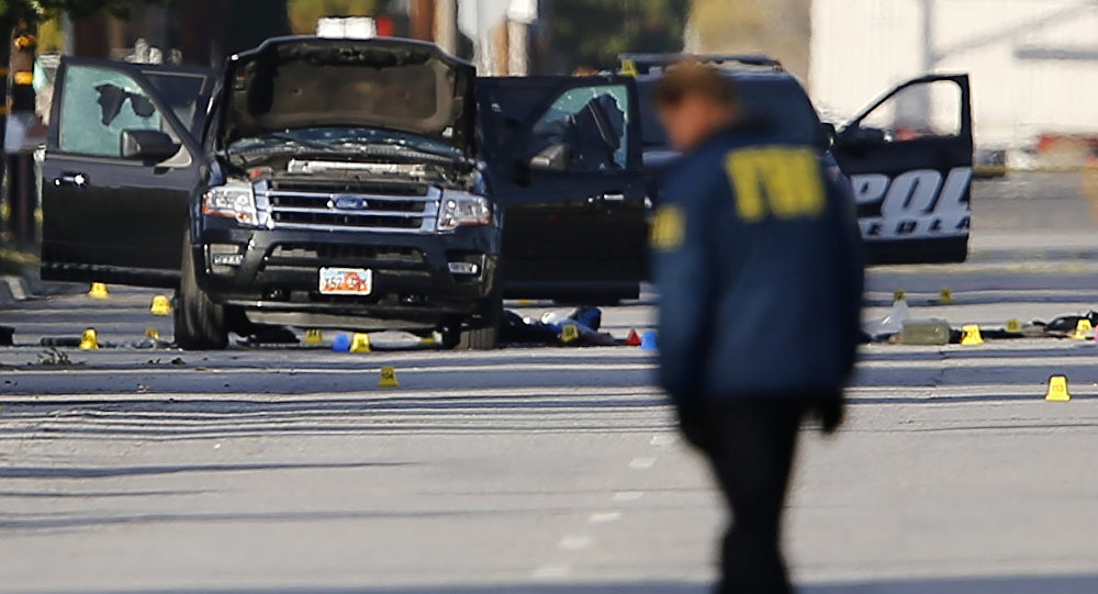 FBI and police continue their investigation around the area of the SUV vehicle where two suspects were shot by police following a mass shooting in San Bernardino, California December 3, 2015