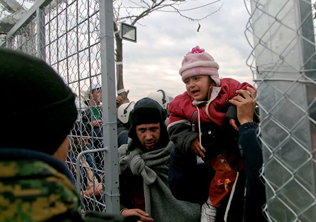 A migrant is child carried into Macedonia, near the southern Macedonian town of Gevgelija, Friday, Dec. 4, 2015.