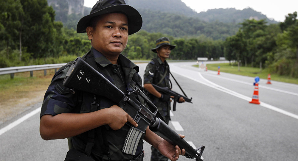 Malaysian Police stands guard at the Malaysia-Thailand border.
