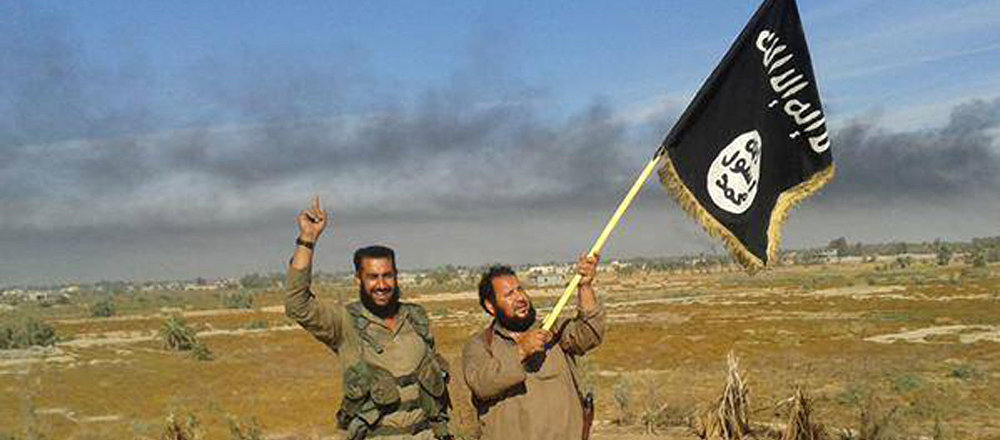 Islamic State militant waves his group's flag as he and another celebrate in Fallujah, Iraq, west of Baghdad